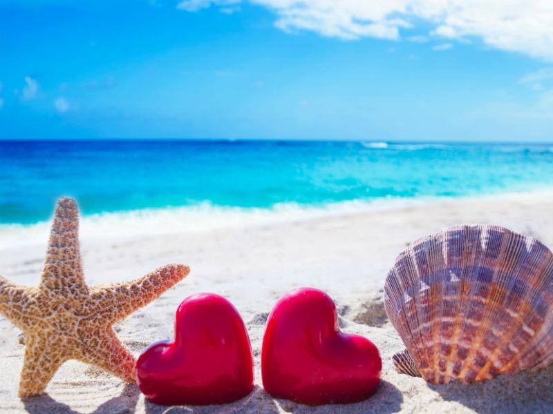 Strand mit Seestern und zwei Herzen und Muschel