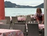 Kellnerin deckt Tische in Gastgarten an Seeufer (Fuschlsee und Schloss Fuschl im Hintergrund)