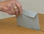 Eine Frau wirft ihre Stimme in die Wahlurne