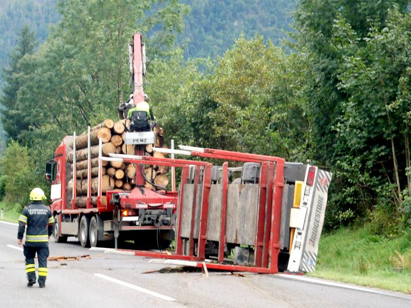Holztransporter umgestürzt Baumstämme Autos getroffen