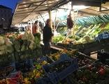 Marktstand auf der Salzburger Schranne in der Dunkelheit mit Kunden
