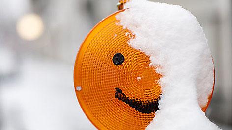 Schneebedeckte Baustellenlampe als Smiley