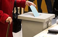 Frau wirft einen Stimmzettel in eine Wahlurne