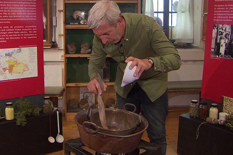 Mann kocht Salbe in Museum