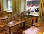 Durch Schulfenster gestoßene Leiter mit Glasscherben in Klassenzimmer