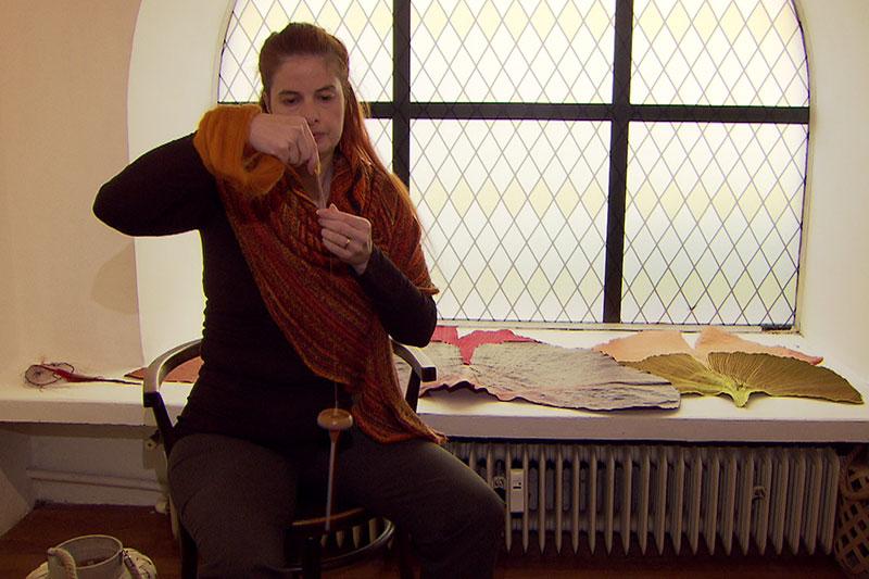 Frau spinnt einen Faden mit einer Handspindel