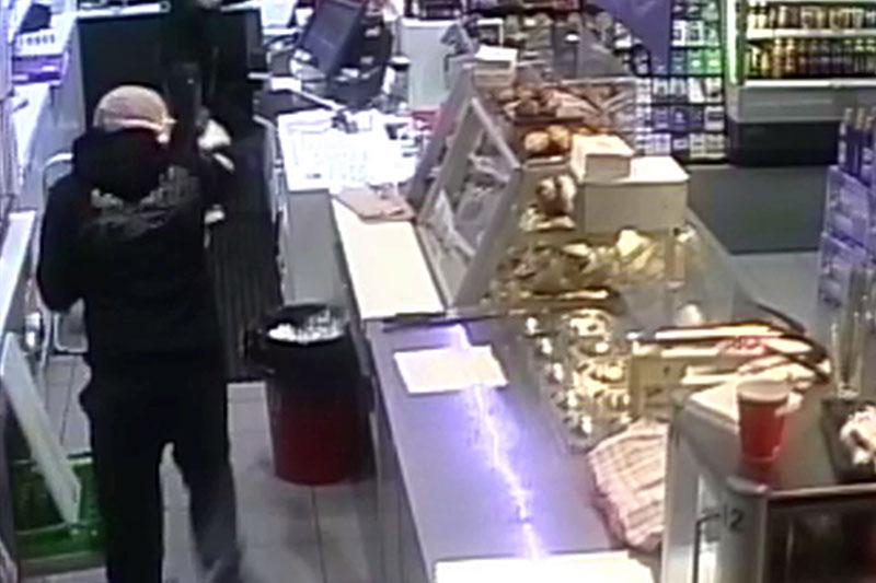 Räuber auf Bild einer Überwachungskamera in einer Tankstelle
