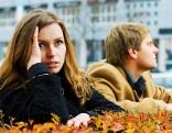 Frau und Mann sitzen voneinander abgewandt