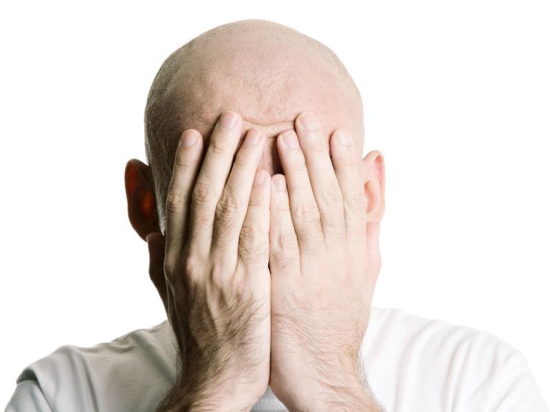 Mann hält sich Hände vors Gesicht