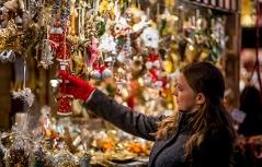 Frau mit Weihnachtskugeln am Adventmarkt