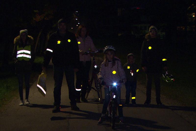 Fußgänger mit Rückstrahlern in der Dunkelheit auf der Straße