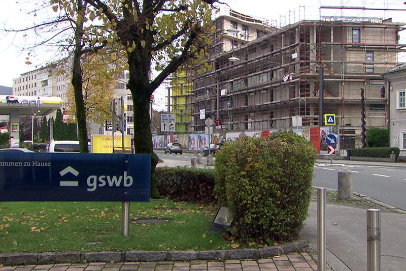 Türschild der Wohnbaugesellschaft GSWB mit Wohnblock Baustelle im Hintergrund