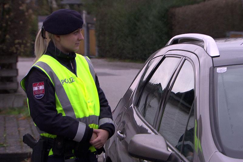 Polizistin steht bei einem Auto (Kontrolle)
