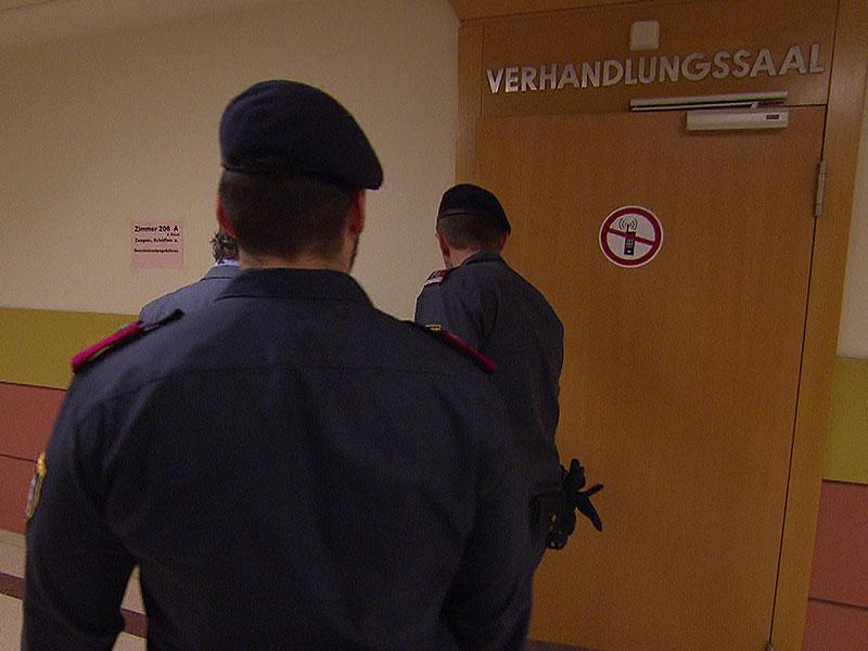 Angeklagter mit Polizisten auf dem Weg in den Verhandlungssaal
