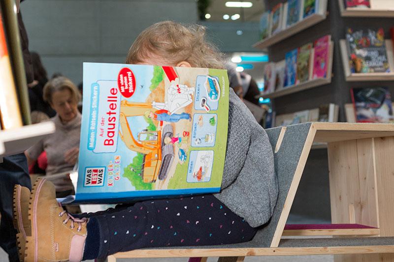 Kind liest auf der Buch Wien
