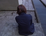 Frau sitzt mit Rücken zur Kamera allein auf Treppe