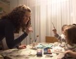 Mutter weist Kind mit Geste darauf hin, ruhig zu sein