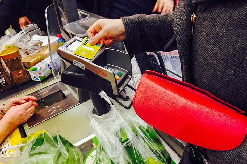 Kunden beim Bezahlen an der Supermarkt Kassa