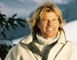 Hansi Hinterseer neben verschneiter Fichte