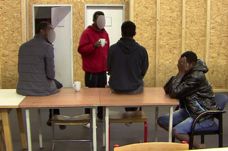 Asylwerber (Flüchtlinge) an Tisch in Asylquartier