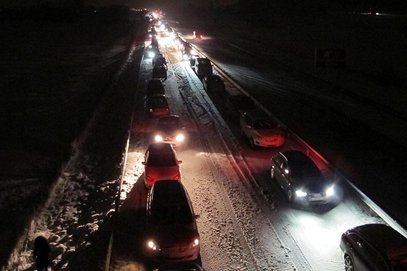 Autos im Stau auf verschneiter Autobahn im Dunkeln (A8 bei Anger)