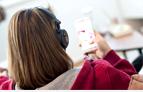 Junger Frau mit Handy und Kopfhörern