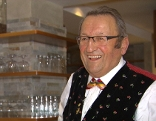 Hotelier Konrad Malfertheiner in Tracht lachend an der Bar
