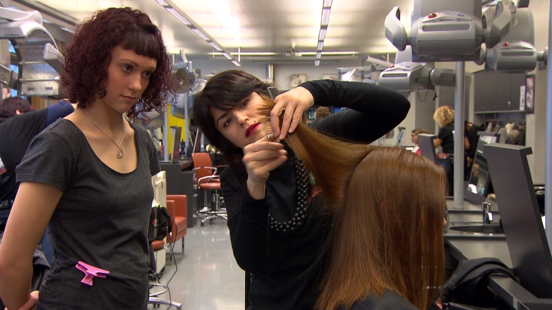 Friseurlehrling macht einer Kundin und Spenderin die Haare