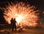 Feuerwerk mit zwei Chinesen im Vordergrund, die gerade ein Feuerwerk zünden