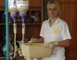 Hauskrankenpflegerin (Altenpflegerin) von einem mobilen privaten Pflegedienst (Hilfswerk) mit Waschschüssel und Infusionsflaschen im Wohnzimmer einer Wohnung