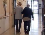 Bewohner in Seniorenheim geht am Arm einer Pflegerin