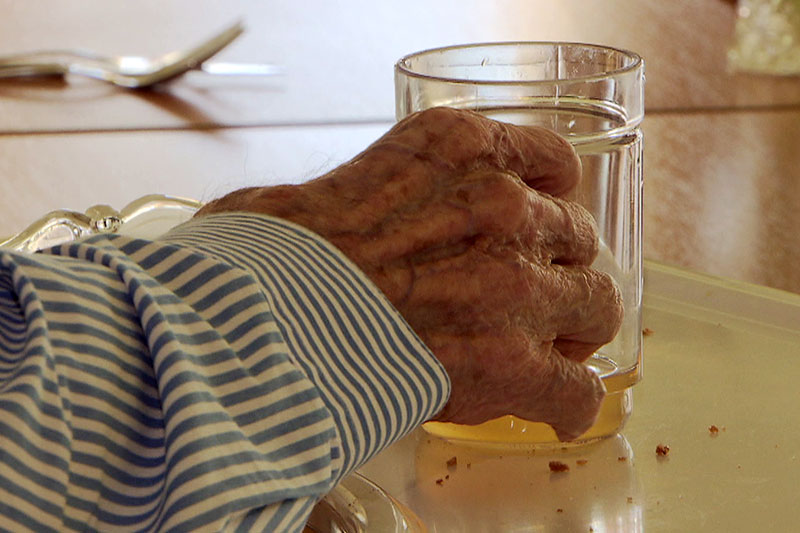 Hand einer Heimbewohnerin mit Saftglas in Pflegeheim