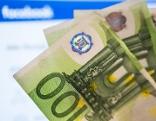 Geld vor Facebook-Logo