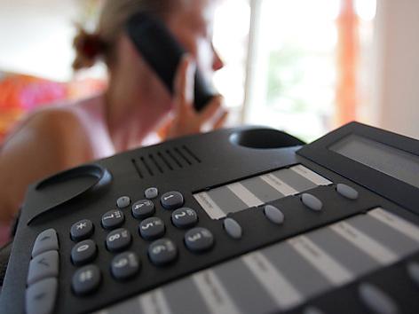 Frau lässt sich am Telefon beraten
