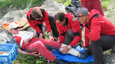 Bergretter verbinden übungsmäßig ein fiktives Unfallopfer.