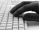 Hand auf Tastatur mit Handschuh
