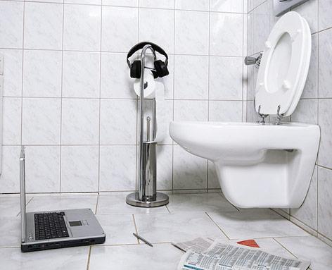 Toilette, Laptop und Zeitung