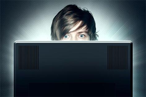 Junger Mann sitzt vor Computer