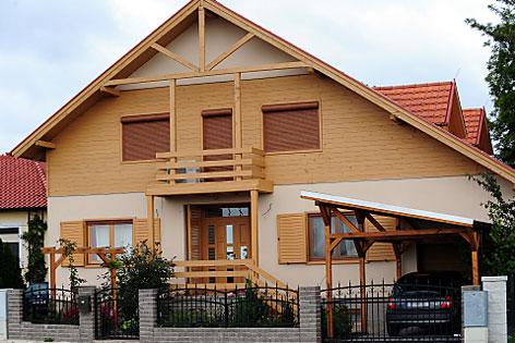 Einfamilienhaus mit brauner Fassade und braunen Rollos