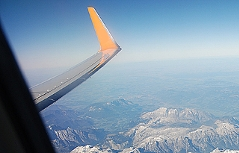 Verkehrsflugzeug im Steigflug über den Bergen.