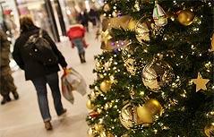 Frau trägt ein Einkaufssackerl durch ein weihnachtlich geschmücktes Einkaufszentrum