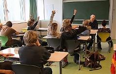 Unterricht in einer Schulklasse, Kinder zeigen auf.