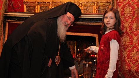 Der griechisch-orthodoxe Bischof Theofilaktos von Bethlehem  übergibt das ORF-Friedenslicht in der Geburtstgrotte an das Friedenslichtkind Sarah Schinwald aus Munderfing