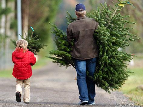 Vater und Tochter nach dem Kauf von zwei Tannenbäumen