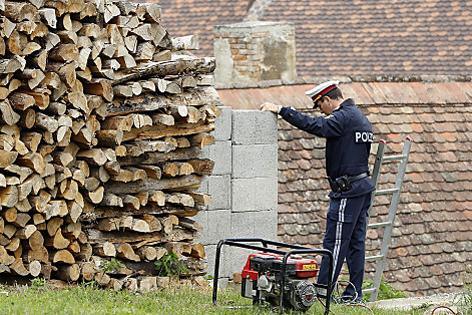 Polizist lehnt an Mauer in der Nähe des Fundorts von Julia Kührer, davor ein Holzhaufen.