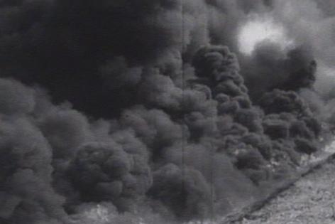 brennendes Feld, davor ein Damm