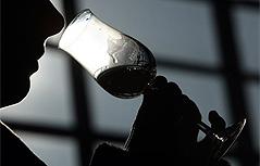 Mann trinkt aus Schnapsglas