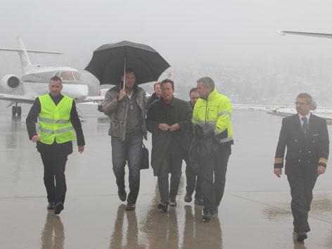 Arnold Schwarzenegger mit Ralf Möller und anderen bei starkem Regen am Innsbrucker Flughafen.