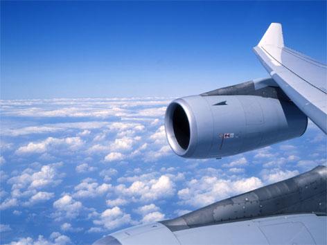 Triebwerk und Fluzeugflügel während eines Fluges über den Wolken