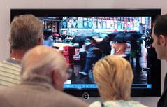Menschen stehen vor einem TV-Gerät